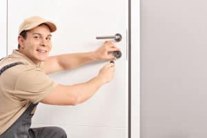 Cheerful locksmith installing a door lock on a new white door and looking at the camera
